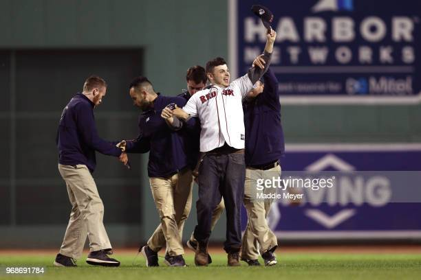 A fan waves to the crowd after rushing the field and being tackled by security during the fifth inning of the game between the Boston Red Sox and the...