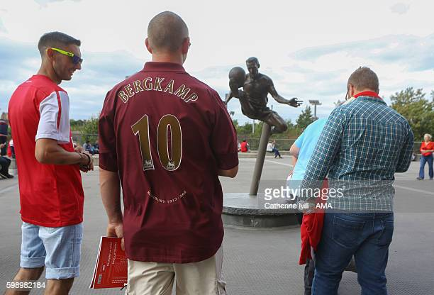 A fan wearing a Dennis Bergkamp shirt looks at the statue of Dennis Bergkamp before the Arsenal Foundation Charity match between Arsenal Legends and...