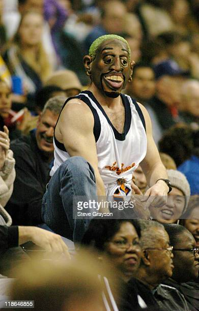Fan wearing a Dennis Rodman mask leads the crowd in cheers during a timeout.