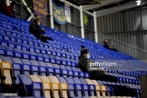 Fan wearing a face mask checks their mobile phone whilst sat in the stands prior to the Sky Bet League One match between Shrewsbury Town and...