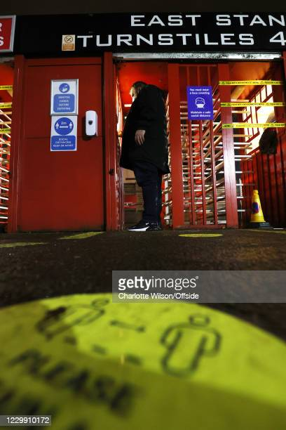 Fan wearing a face mask enters the turnstiles at The Valley ; a sticker asking people to socially distance is stuck to the pavement in the foreground...