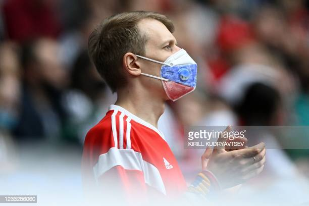 Fan wearing a face mask painted in the colours of the Russian national flag watches the friendly football match Russia v Bulgaria in Moscow on June 5...