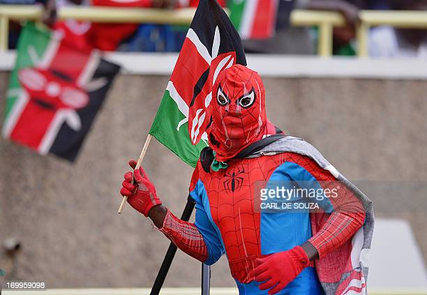 A fan wearing a Kenyan flag and dressed as spiderman looks on before the 2014 World Cup Qualifying match between Nigeria and Kenya at the Kasarani...