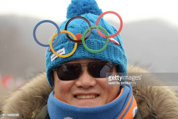 A fan wearing a knit cap with the Olympic rings smiles as the start of the Alpine Skiing Women's Slalom was delayed due to weather conditions at the...