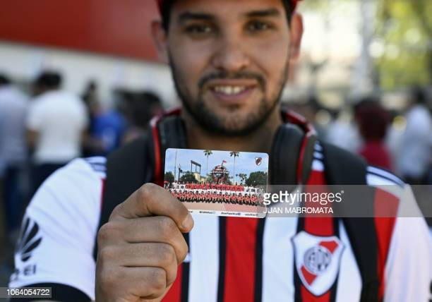 A fan wearing a River Plate's jersey poses with his ticket for the Copa Libertadores superclasico second leg final football match against Boca...