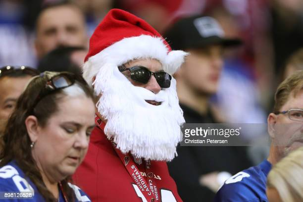 A fan wearing a Santa Claus hat and beard watches the NFL game between the New York Giants and Arizona Cardinals at University of Phoenix Stadium on...