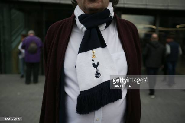 A fan wearing a Spurs scarf arrives to attend the Legends football match between Spurs Legends and Inter Forever the second and final test event for...