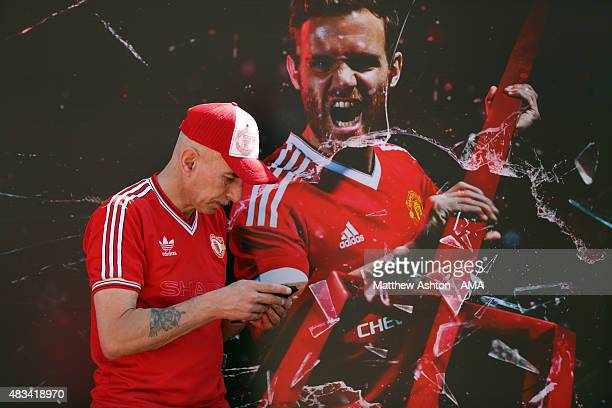 A fan wearing an Adidas kit from the 1980's stands next to a poster of the new campaign with Juan Mata of Manchester United advertising the new...