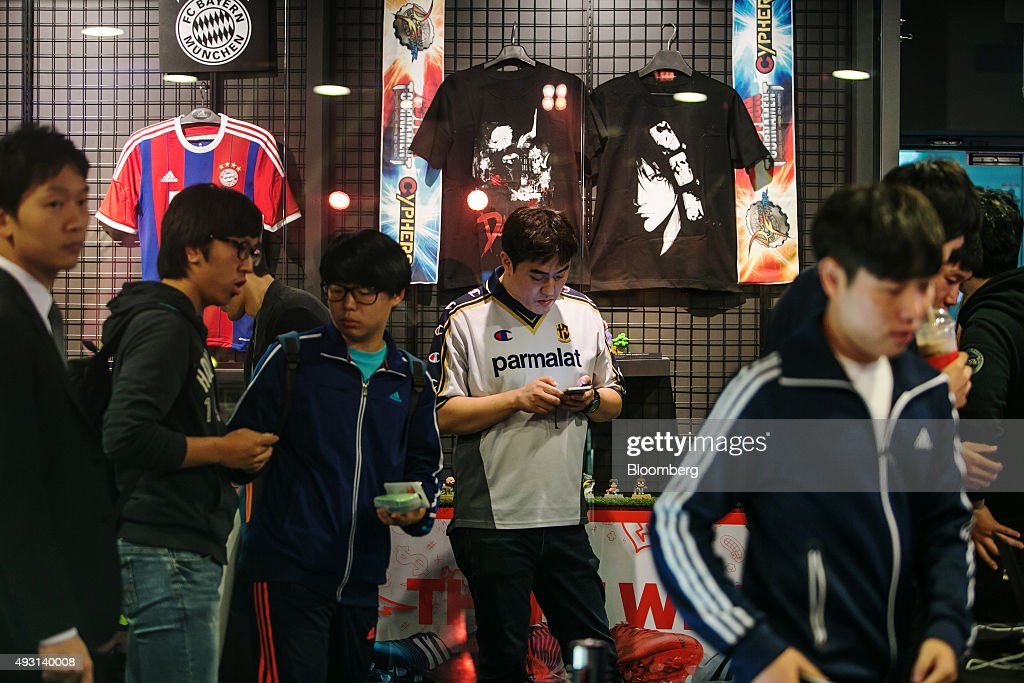 A fan wearing an Parma AC soccer jersey, center, uses a smartphone while standing in line to collect tickets prior to the final round of the Electronic Arts Inc. (EA) Sports FIFA Online Championship at the Nexon Co. e-Sports Stadium in Seoul, South Korea, on Saturday, Oct. 17, 2015. Video game competitions, known as eSports, have been expanding as gamers seek to shift perceptions around their craft from a basement hobby to a serious money making industry. Photographer: Jean Chung/Bloomberg via Getty Images