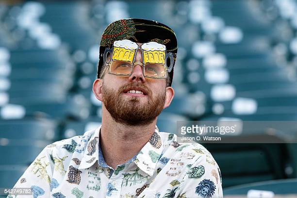 A fan wearing beer goggles sits in the stands before the game between the Oakland Athletics and the Milwaukee Brewers at the Oakland Coliseum on June...
