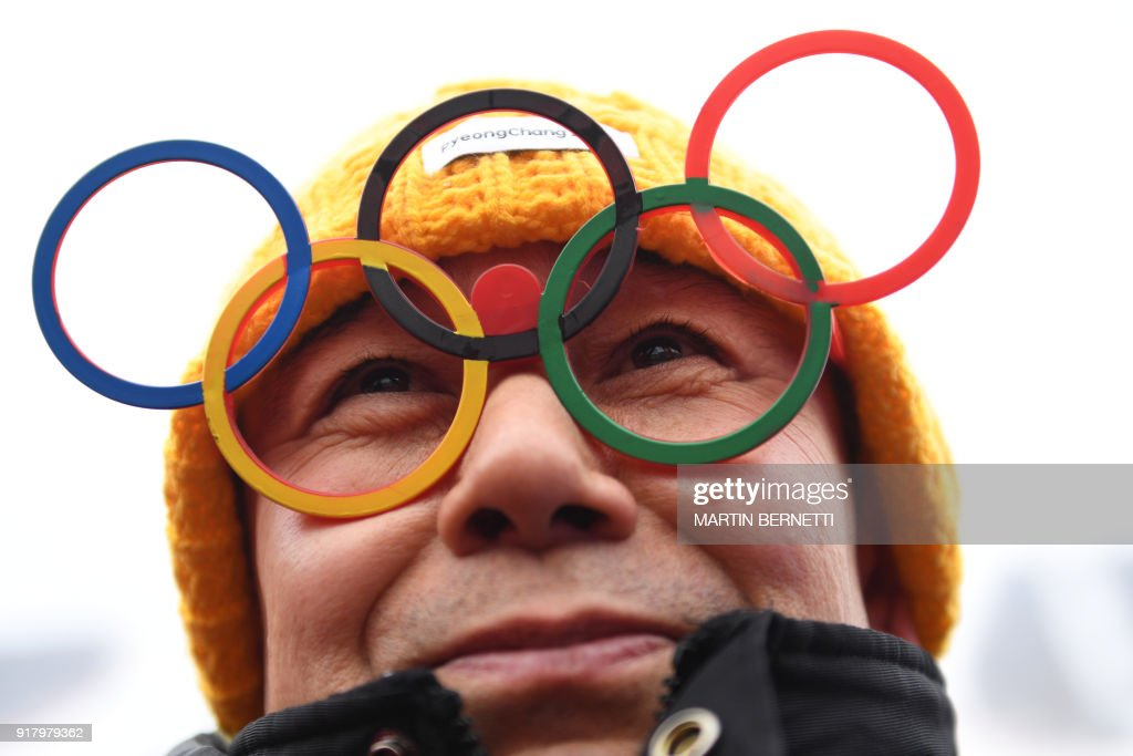 TOPSHOT - A fan wearing eyeglasses shaped like Olympic rings smiles while waiting for the Alpine Skiing Women's Slalom that was later cancelled due to weather conditions at the Jeongseon Alpine Center during the Pyeongchang 2018 Winter Olympic Games in Pyeongchang on February 14, 2018. / AFP PHOTO / Martin BERNETTI