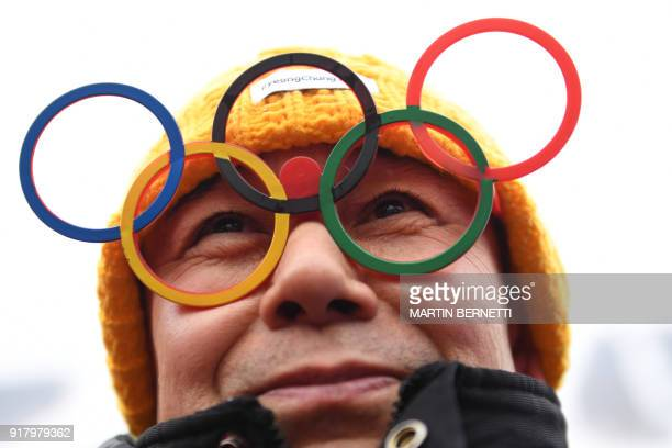 TOPSHOT A fan wearing eyeglasses shaped like Olympic rings smiles while waiting for the Alpine Skiing Women's Slalom that was later cancelled due to...