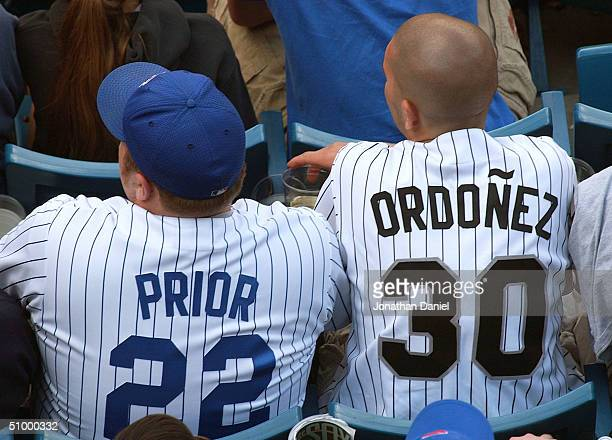 A fan wearing the jersey of Chicago Cub pitcher Mark Prior sits next to a fan wearing a jersey of Chicago White Sox outfielder Magglio Ordonez during...