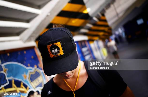 A fan wears a cap with an image of Diego Maradona former Boca Juniors player and coach of Gimnasia y Esgrima La Plata before a match between Boca...