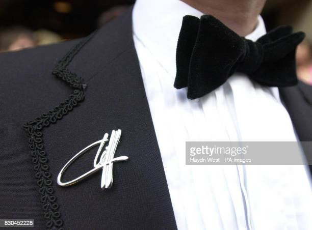 A fan wears a Cliff broach as he arrives at the Grosvenor House Hotel in London for a charity party on the occasion of Sir Cliff Richard's 60th...