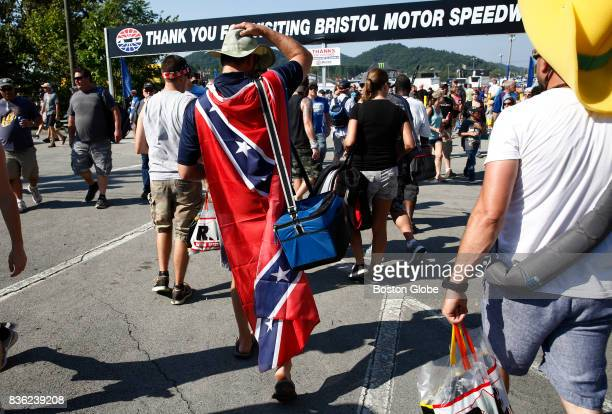 NASCAR fan wears a Confederate flag around his shoulders as he walks towards a private campground area that hosts vendors food and entertainment...