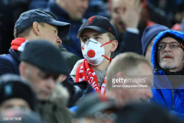 A fan wears a face mask in light of the growing Coronavirus concerns during the UEFA Champions League round of 16 second leg match between Liverpool...