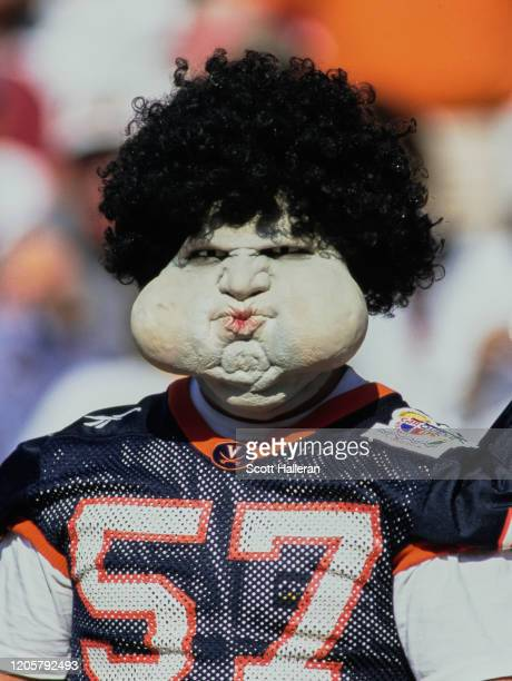 Fan wears a fancy dress mask during the NCAA Atlantic Coast Conference college football game between the University of Virginia Cavaliers and the...