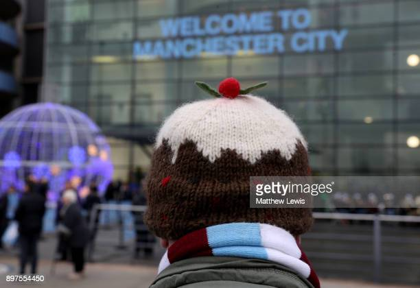 A fan wears a festive hat outside the ground prior to the Premier League match between Manchester City and AFC Bournemouth at Etihad Stadium on...