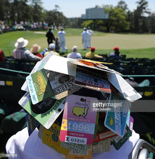 A fan wears a hat covered in Masters passs at the 18th green during the first round of the Masters golf tournament at Augusta National Golf Club on...
