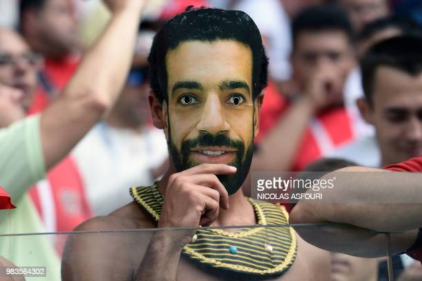 Fan wears a mask with the face of Egypt's forward Mohamed Salah before the Russia 2018 World Cup Group A football match between Saudi Arabia and...
