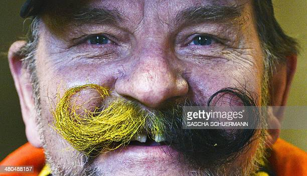 A fan wears a mustache in the colors of his team Borussia Dortmund prior to the German first division Bundesliga football match Borussia Dortmund vs...