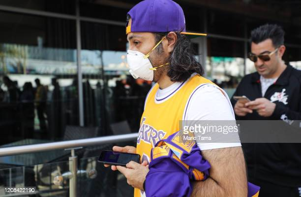A fan wears a protective mask as people wait in line to attend the 'Celebration of Life for Kobe and Gianna Bryant' memorial service at Staples...