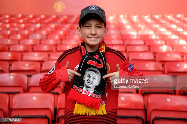 A fan wears a scarf displaying an image of Ole Gunnar Solskjaer Interim Manager of Manchester United on it prior to the Premier League match between...