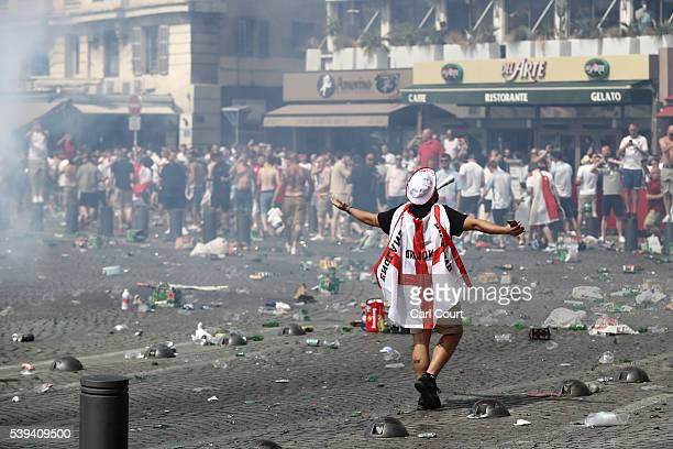A fan wears the Englad flag colors as rubbish lines the streets as England fans gather cheer and clash with police ahead of the game against Russia...