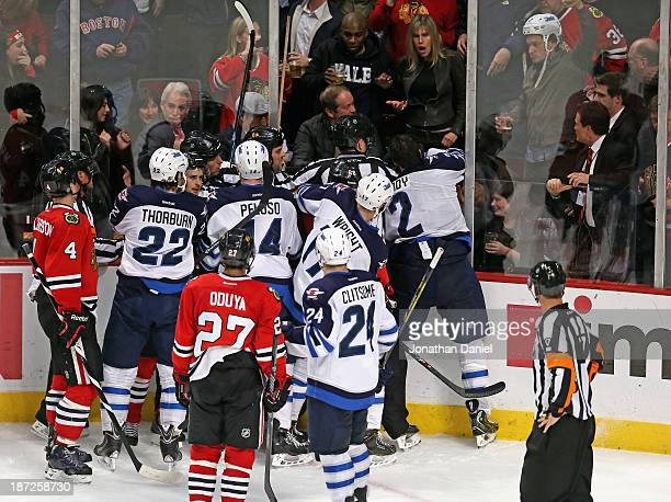 A fan wears the helmet of Adam Pardy of the Winnipeg Jets after pulling it off of his head after Pardy was checked through the glass by Brandon...