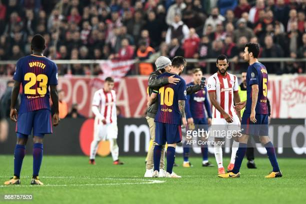 A fan who invaded the pitch takes a selfie picture with Barcelona's Argentinian forward Lionel Messi during the UEFA Champions League group D...