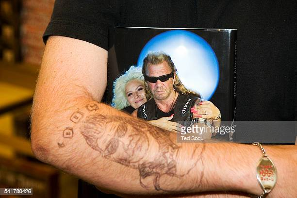 A fan with a makeshift 'Dog' tattoo holding the book 'You Can Run But You Can't Hide' at Duane 'Dog the Bounty Hunter' Chapman's book signing at...