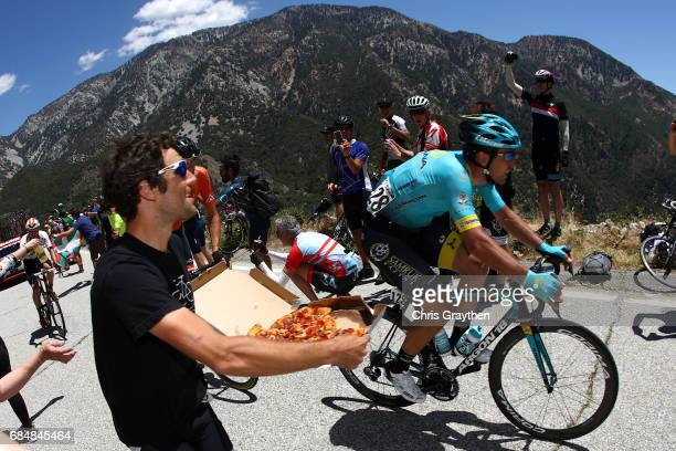 A fan with a pizza runs alongside of Artyom Zakharov of Kazakhstan riding for Astana Pro Team during stage five of the AMGEN Tour of California from...