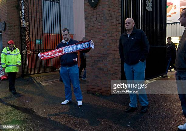 A fan with a scarf bearing the names of Liverpool and Northampton Town football clubs outside the Shankly Gates at Anfield before the team's Carling...