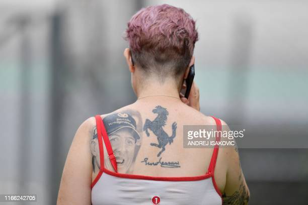 A fan with a tattoo showing the Scuderia Ferrari logo and a picture of former German Formula One champion Michael Schumacher is seen ahead of the...