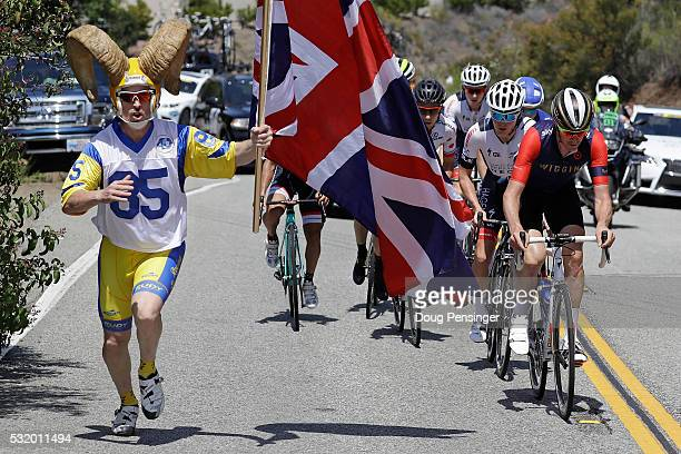 A fan with a Union Jack runs on the road as Andrew Tennant of Great Britain riding for Team Wiggins leads the breakway on the climb of Westlake Blvd...