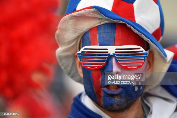 TOPSHOT A fan with half his face painted with the Icelandic flag and the other half with the Croatian one poses before the Russia 2018 World Cup...