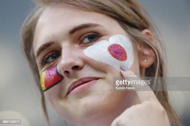 A fan with her face painted with Japanese and Belgian national flags cheers ahead of a World Cup roundof16 match between Japan and Belgium in...