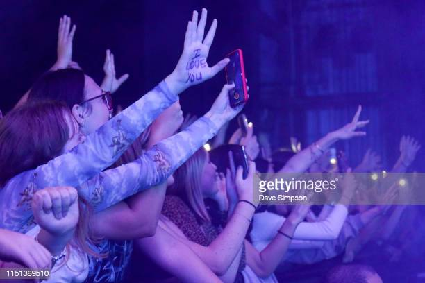 Fan with 'I LOVE YOU' written on her hand waves as Ruel performs at the Bruce Mason Centre on May 24, 2019 in Auckland, New Zealand.