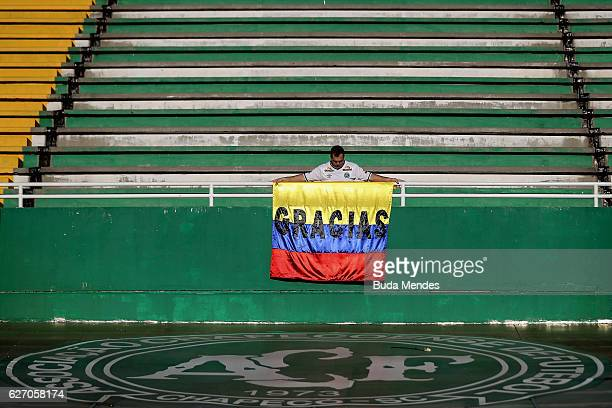 Fan with the symbolic flag of Colombia paying tribute to the players of Brazilian team Chapecoense Real at the club's Arena Conda stadium in Chapeco,...