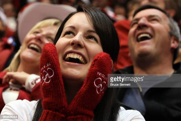 A fan with Vancouver Olympic red mittens smiles during a period break in the game between Canada and Finland during the ice hockey women's semifinal...