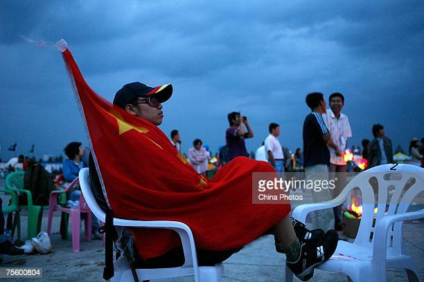 A fan wraps himself with a Chinese national flag at the first 'Green Flag Erdos Grassland Rock Music Festival' near the Mausoleum of Genghis Khan on...