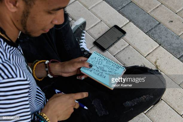 A fan writes a note to leave at the makeshift memorial outside the XXXTentacion Funeral Fan Memorial at BBT Center on June 27 2018 in Sunrise Florida