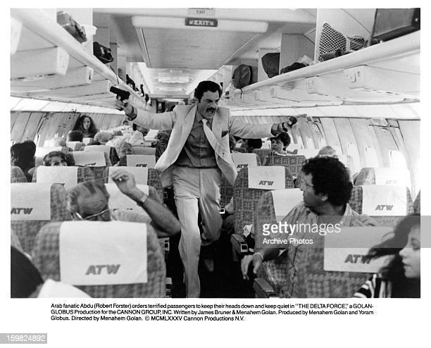 Fanatic Robert Forster orders terrified passengers to keep their heads down and keep quiet in a scene from the film 'The Delta Force' 1986