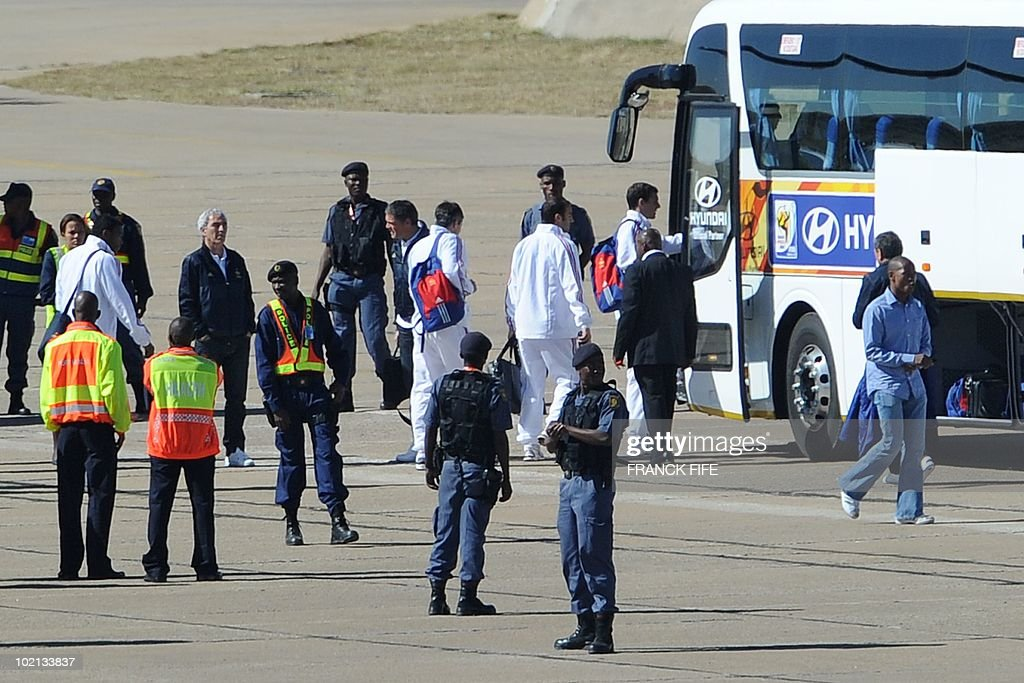 Fance's football national team's coach Raymond Domenech (L, white hair) and team members arrive at the airport in Polokwane on June 16, 2010. France will play against Mexico in their second first-round match of the 2010 Football World Cup on June 17.