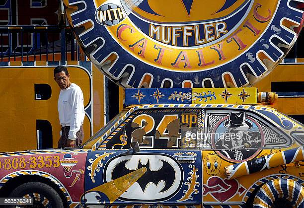 A fanciful car parked in front of a muffler shop catches the eye of a passerby on Whittier Boulevard in East Los Angeles