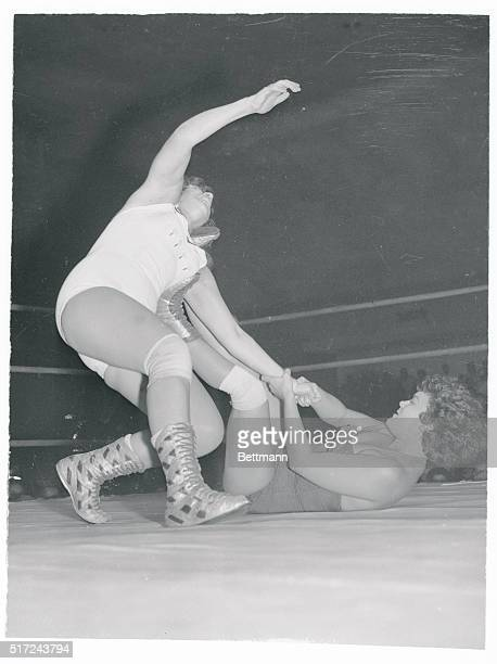 Fancy boots or no fancy boots lady wrestler Betty Larkin is in real trouble as Jerry Ford gets a grip on her left arm and pushes her away with a foot...