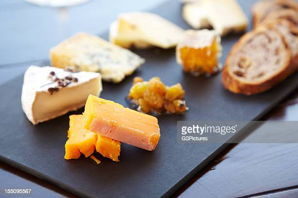 fancy cheese plate with bread and honey - nut food stock photos and pictures