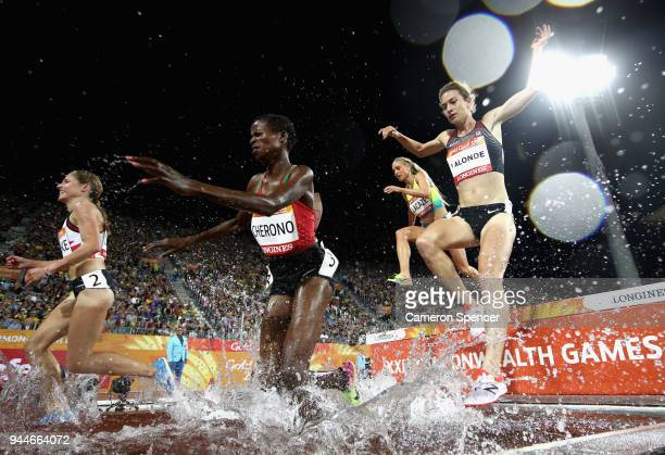 Fancy Cherono of Kenya and Genevieve Lalonde of Canada clear the water jump competes in the Women's 3000 metres Steeplechase final during athletics...