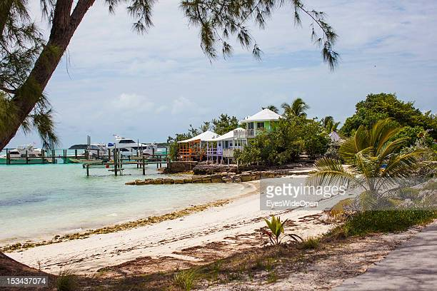 Fancy coloured typical bahamian houses at a white sandy beach with palm trees and luxury yachts at the Staniel Cay Yacht Club on June 15 2012 in The...